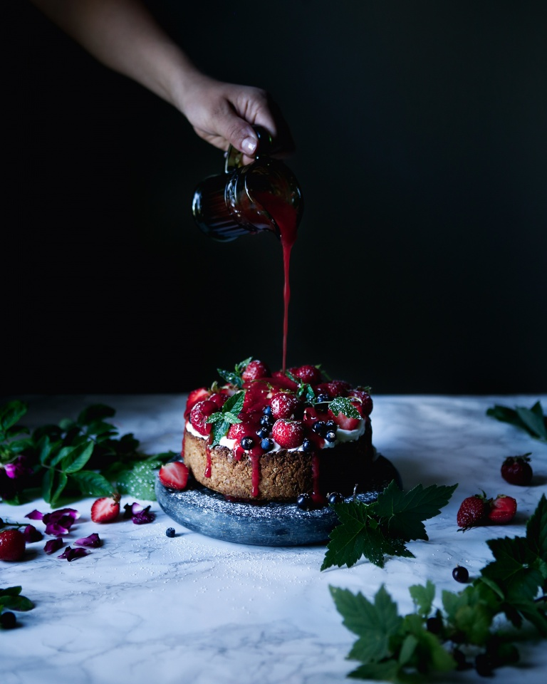 Pouring berry syrup on a granola cake