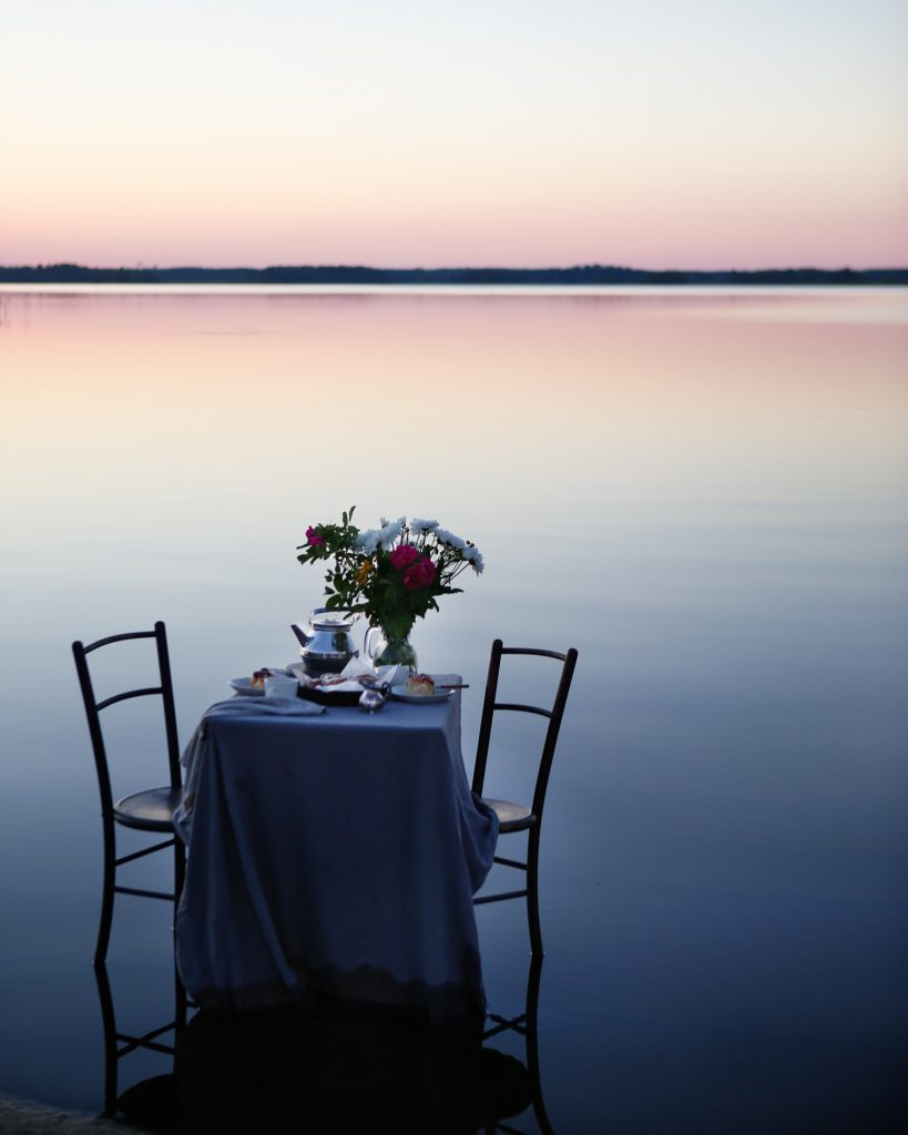 Outdoor dinner by a still lake