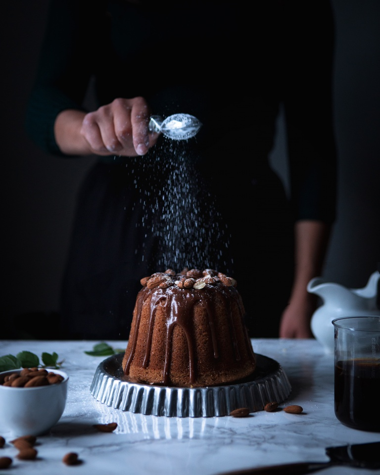 Dusting a bundt cake with powdered sugar